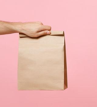 茶色の紙袋を持っている手