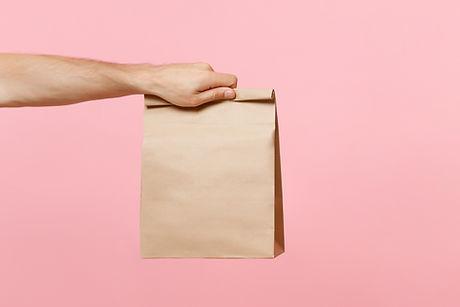 Mano que sostiene la bolsa de papel marr