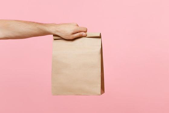 Ruka držící hnědý papírový sáček