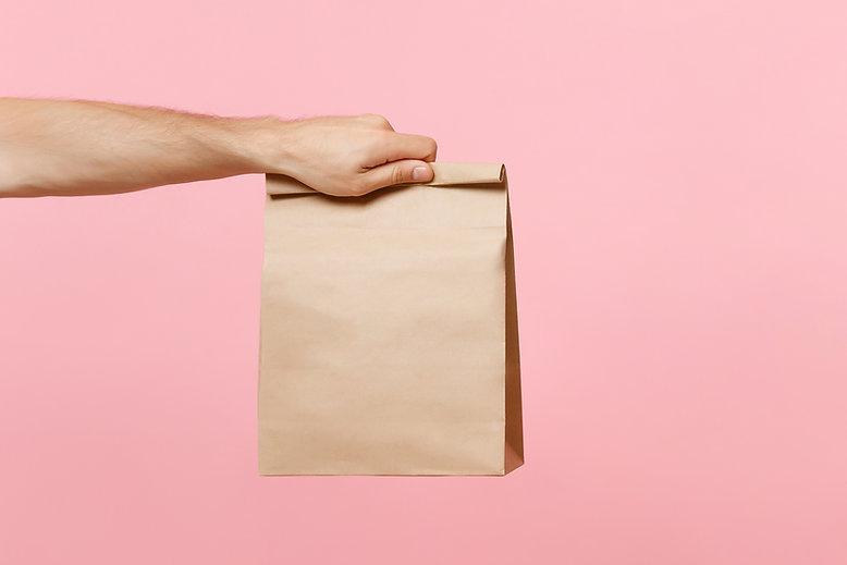 Hand, die braune Papiertüte hält