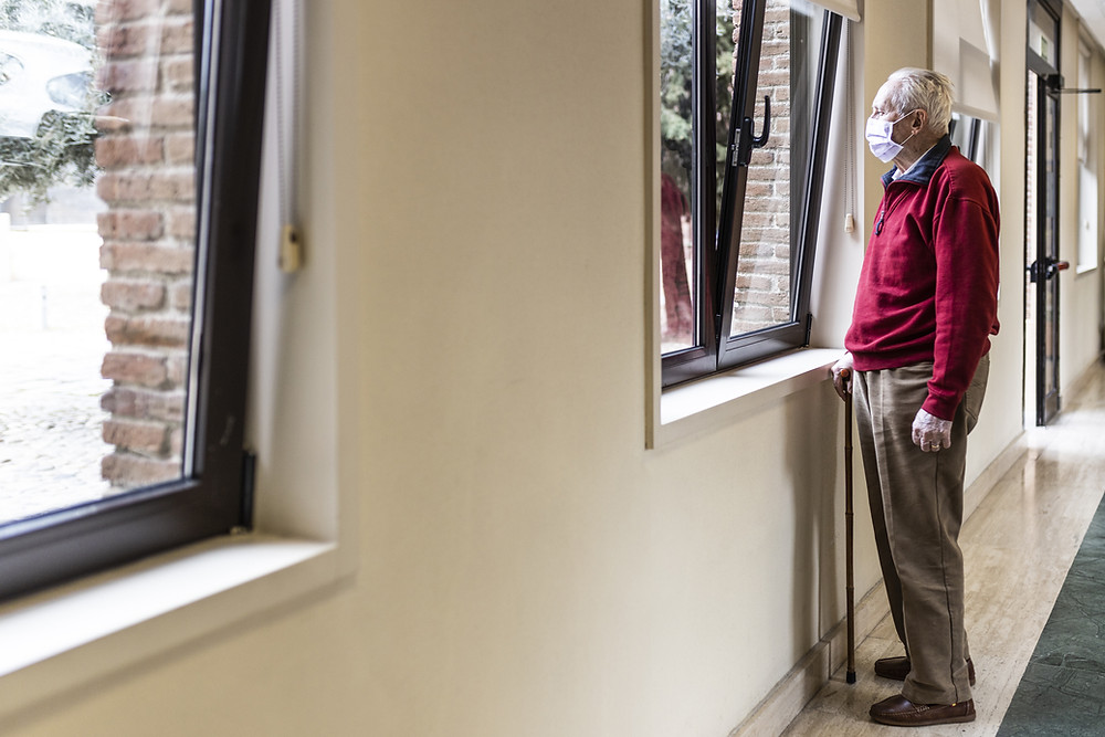 A male senior wearing a red sweater and a mask, while holding a cane is looking out the window