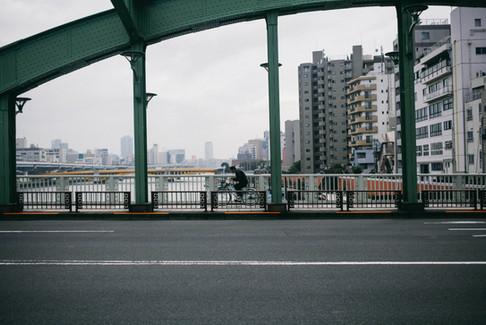 橋を渡る自転車の男性