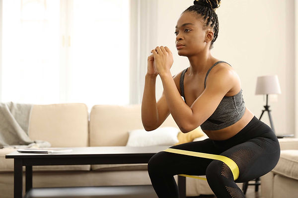 A woman is doing squats in her living room
