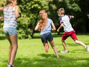 Children Running On Green Grass