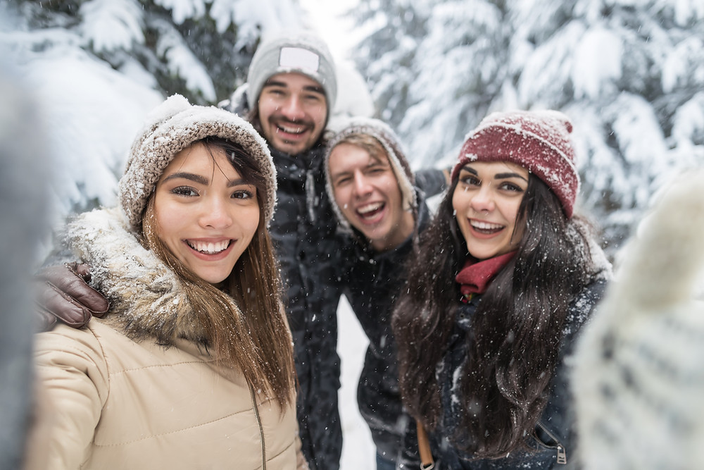 Group of friends taking a selfie in a nature walk in winter. Making friends in adulthood is hard but can be done with these tips from Marble Wellness.