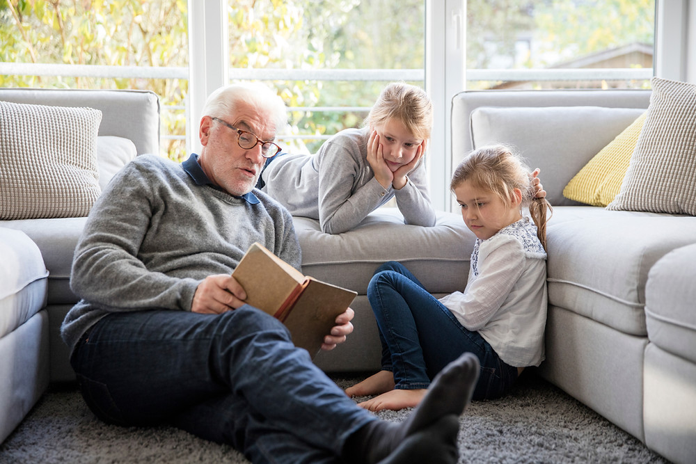 Grandpa reading a story to his granddaughters by the couch