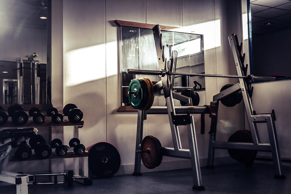 a squat rack in a gym surrounded by dumbbells and exercise equipment