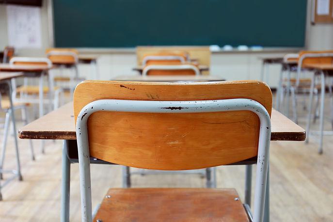 Leere Schulbänke und Stühle