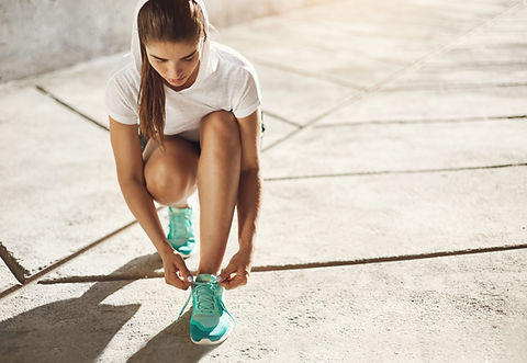 Younger woman bending down to tie her shoelaces in anticipation of a run