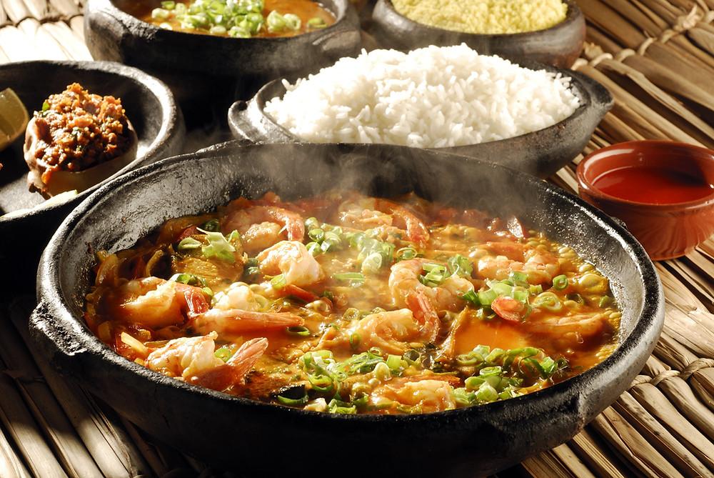 Cardápio de pratos variados de comida servidos em panelas de barro sobre uma mesa rústica