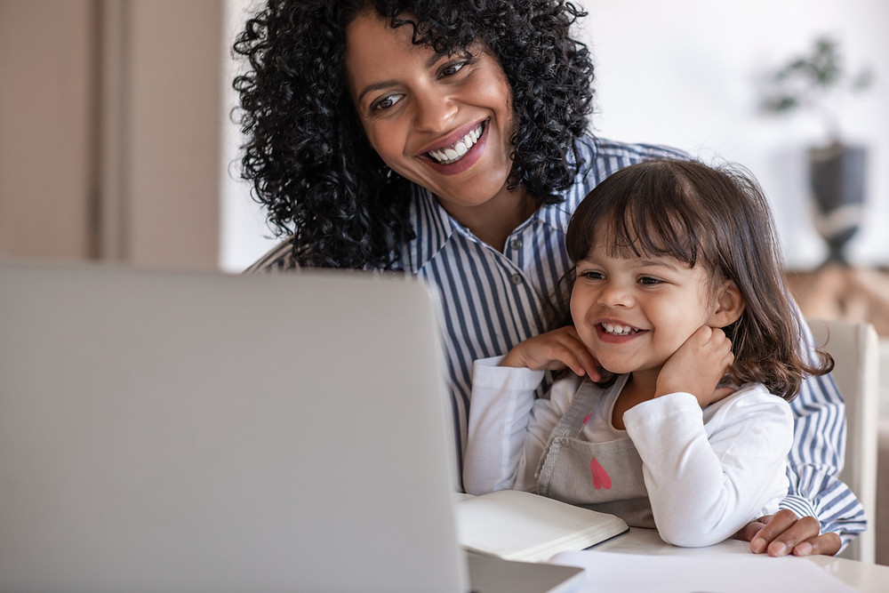 Mother and daughter on a laptop smiling and videoconferencing with someone online