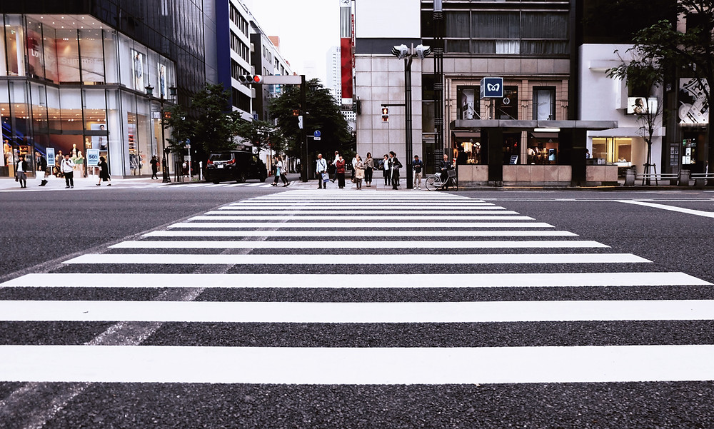 pedestrians on opposite side of crosswalk in city.  showing concept of pedestrian definition