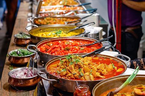 Il s'agit d'un buffet avec des plats dans de grandes casseroles . Il y a des plats rouge, jaune ou orange. Chaque plat à une grosse cuillère afin de pouvoir se servir