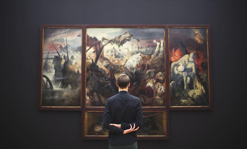Man looking at paintings at a museum