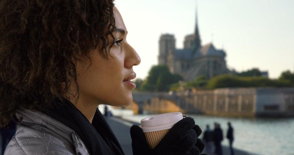 Femme tenant un café face à la Seine