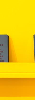 Книги на желтой стене