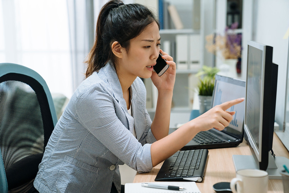woman on phone looking at computer monitor