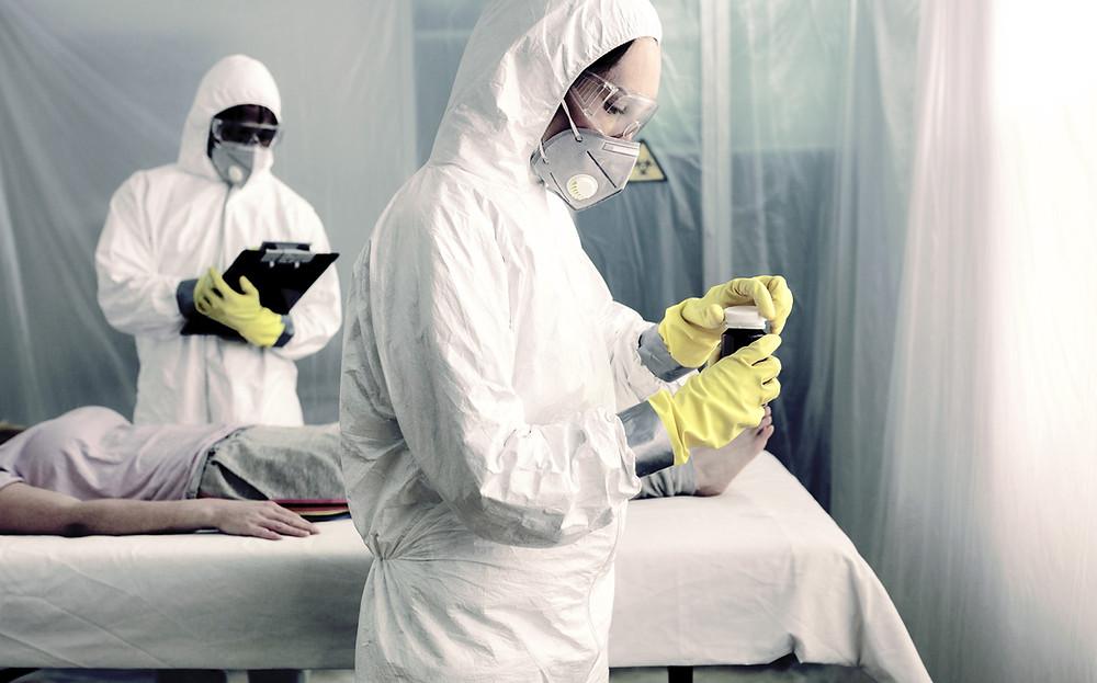 Dos personas con trajes especiales analizan muestras
