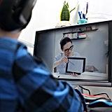 Ein Lerner sitzt mit seinem Lehrer am Computer und macht online Sprachunterricht.