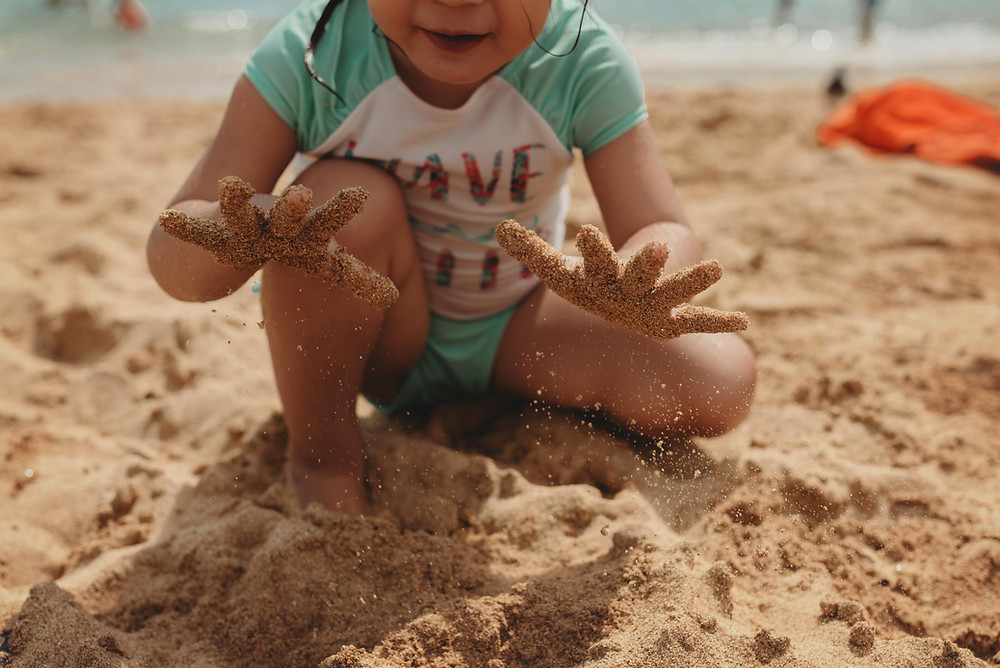 Child playing in sand on UK beach - Nanny