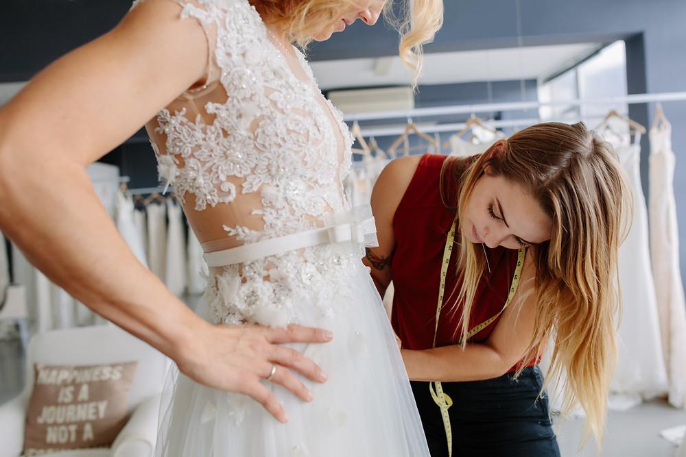 I fornitori li seleziono io: una sarta prende le misure di un abito ad una sposa