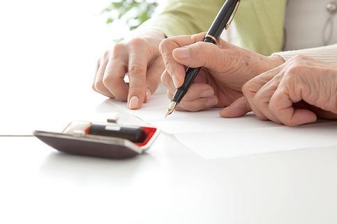 書類を記入するシニア女性とミドル女性 高齢者がサインする手元