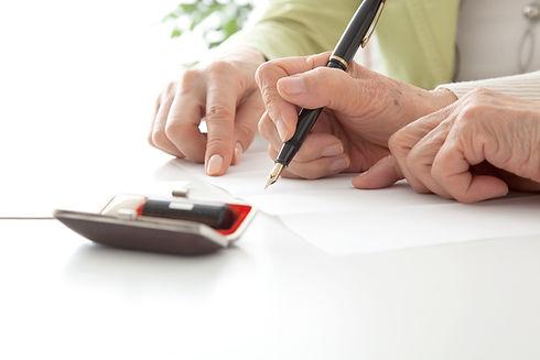 書類を記入するシニア女性とミドル女性 高齢者がサインする手元 顔なし