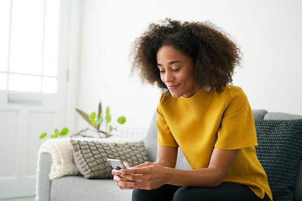 Fotografia de uma mulher sentada em um sofá com celular na mão digitando. Não é possível ver seu rosto.