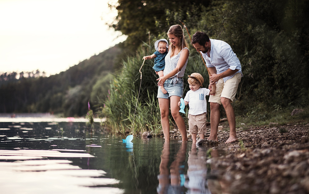 Family with a kid and a baby on vacations having fun at the lake.