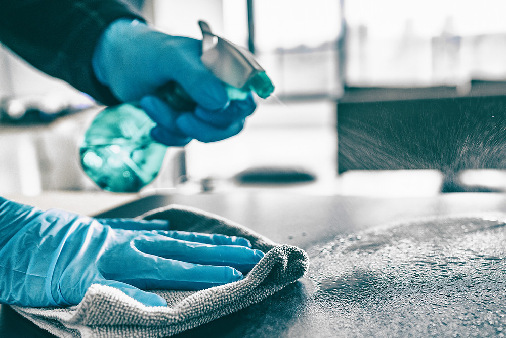 blue gloved hands holding a spray bottle and wiping down a surface