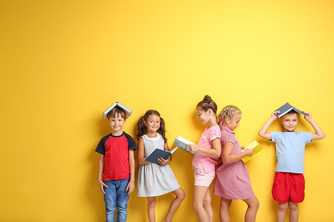 Five children holding and reading books along a yellow wall. Two boys have books on their head. Adelaide Speech Pathologist.