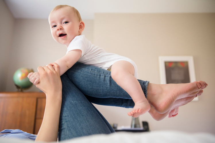 Mother Balancing Baby on Legs