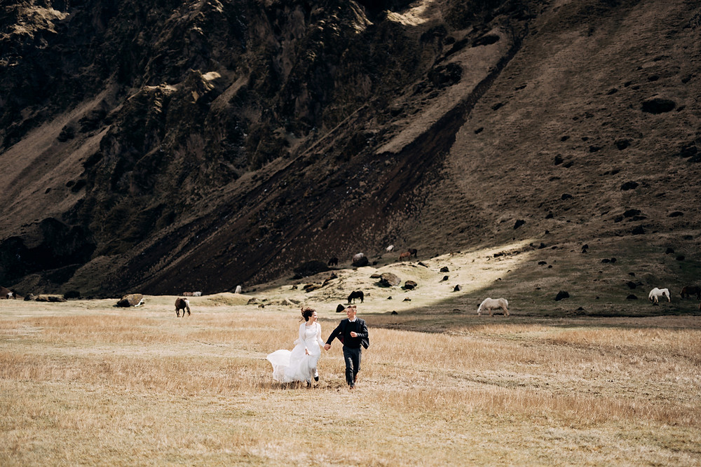 Newlyweds walking through the field during their adventure elopement abroad