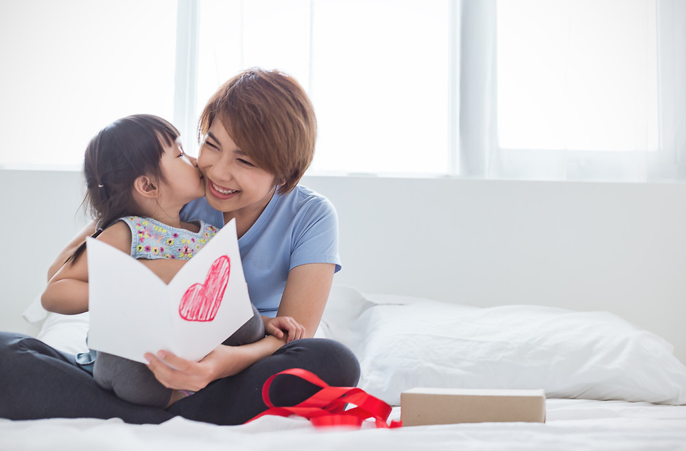 Little girl kissing mother while giving her Mother's Day card