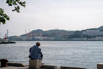 海辺で腰掛ける男性
