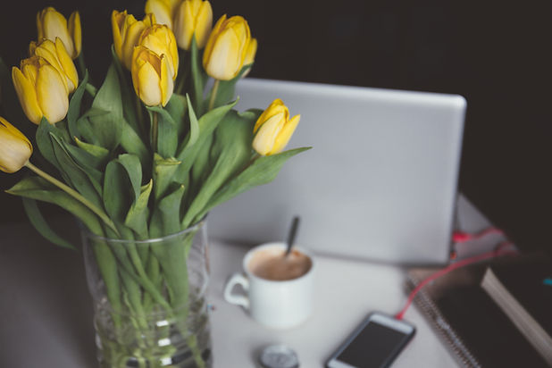 Yellow Flowers and Laptop with a coffee cup on top of a desk.