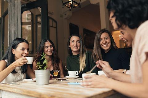 Un groupe de femmes se réunissent pour discuter en buvant un café ou un thé