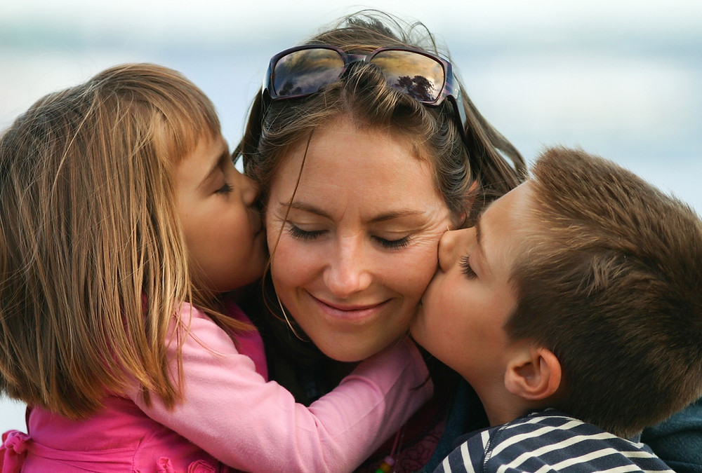 Two kids kiss their mother as she accepts the things she cannot change about motherhood. Catalyss Counseling provides treatment for women's issues in Colorado through online therapy and in person counseling in the Denver area 80209 and 80210