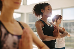 Yoga students in a donation-based community vinyasa yoga class practicing meditation