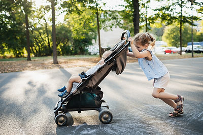 Schwester schiebt Kinderwagen