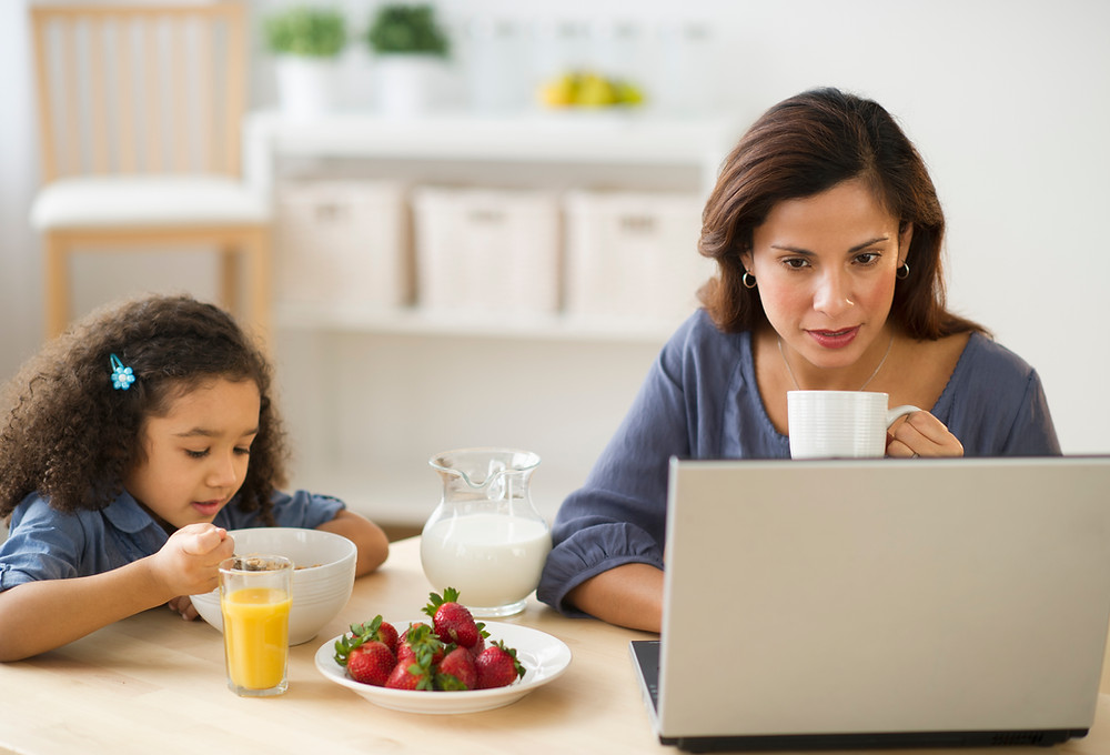 Mom and daughter sit at table, mom is working while daughter eats breakfast, she suffers from mom guilt. Catalyss Counseling provides treatment for women's issues in Colorado through online therapy and in person counseling in the Denver area 80209 and 80210