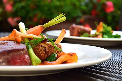 Un plat composé d'un morceaux de viande ou volaille ayant de la panure, de chanterelles, de carottes et d'herbes aromatiques, le tout dans une assiette blanche