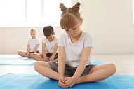 Three children participate in a therapeutic yoga class