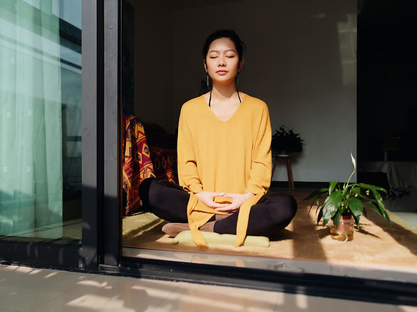 An asian woman in a yellow shirt is seated cross legged on the floor, just inside a sliding door. Her thumbs are touching and her hands interlocked, her eyes are shut, she is appearing serene. A small plant is to her left. She appears to be in meditation.