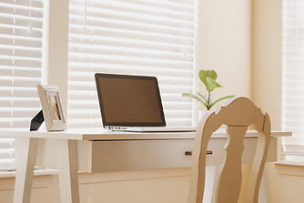 small white desk, painted antiqued chair facing desk, on desk small open laptop in middle section, small standing picture frame on left and plant on right side. Behind is white blinds drawn down, and white walls.