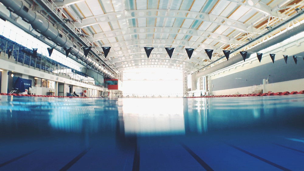 Large indoor swimming pool with flags set up for competition.