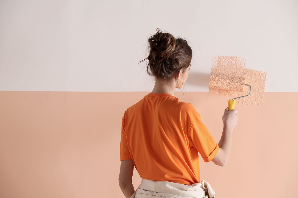 woman painting wall a light pink color at Ash Street Cooperative il