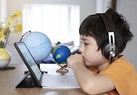 A boy with headphones learning at a computer