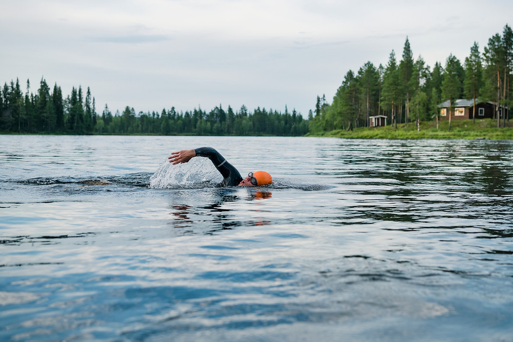 A person in a wetsuit and orange swim cap swimming in an outdoors lake surrounded by trees and a cabin in the distance