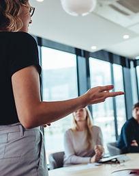 Image représentant une formation. Une femme se tient debout et explique des choises à des personnes qui la regardent et l'écoutent.